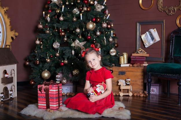 Leuk meisje houdt een speelgoed van de notenkraker in de buurt van de kerstboom en cadeau