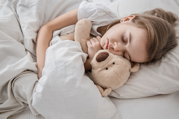Leuk meisje in bed met zacht stuk speelgoed.
