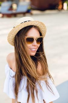 Leuk meisje in bruine zonnebril en strooien hoed glimlacht charmant.