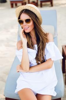 Leuk meisje in bruine zonnebril en strooien hoed glimlacht wijd en houdt haar hand in de buurt van de kin
