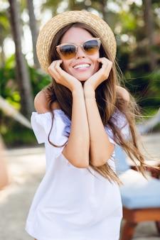 Leuk meisje in bruine zonnebril en strooien hoed glimlacht wijd en houdt haar handen in de buurt van de kin.
