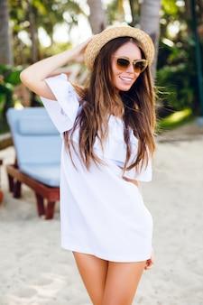 Leuk meisje in bruine zonnebril en strooien hoed glimlacht wijd en houdt haar hoed met een hand vast