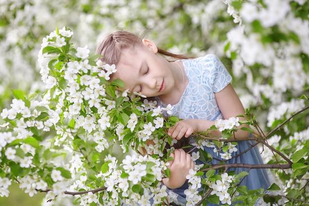 Leuk meisje in de bloeiende tuin van de appelboom bij de lente