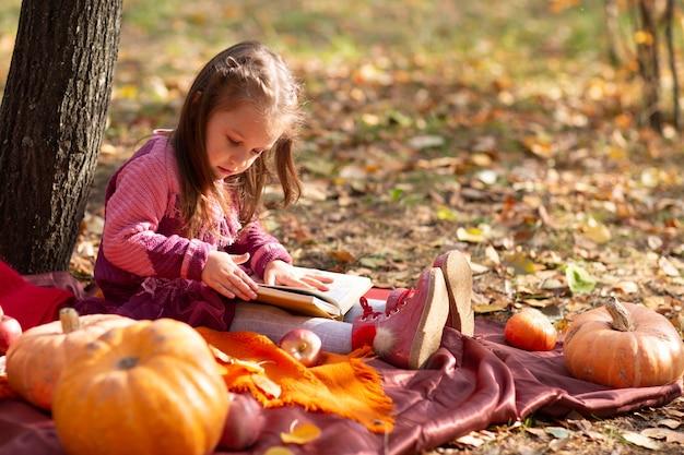 Leuk meisje in de herfstpark met boeken en oranje kleurenbladeren en gele pompoen