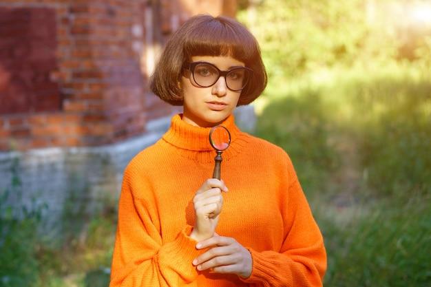 Leuk meisje in de natuur met een vergrootglas in haar handen ,.