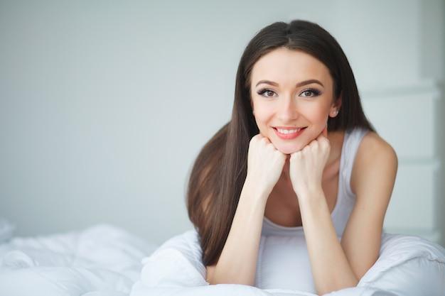 Leuk meisje in de ochtend op een wit bed