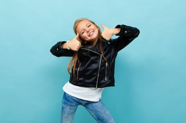 Leuk meisje in een casual look met een leren jas en spijkerbroek toont klasse op een lichtblauwe achtergrond.