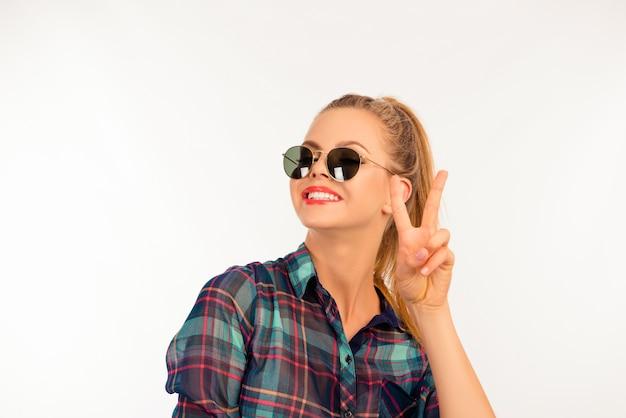 Leuk meisje in een geruit overhemd met zonnebril met twee vingers