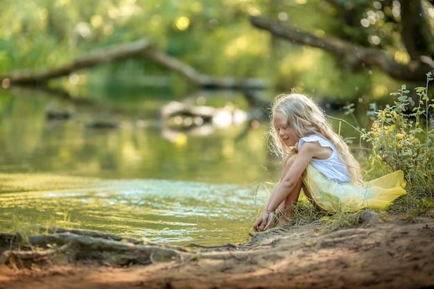 Leuk meisje in een jurk in een donker bos op de achtergrond van de rivier