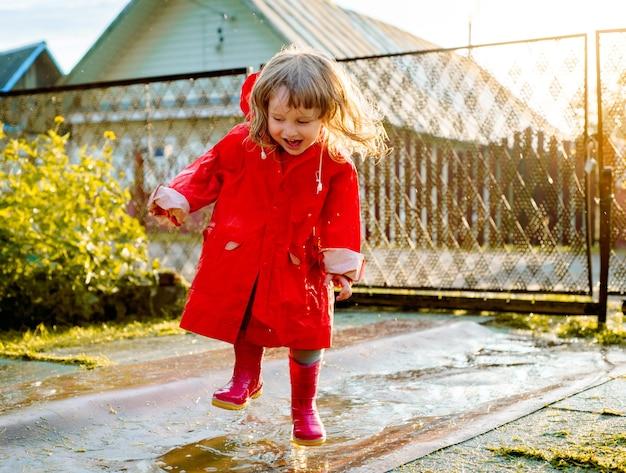 Leuk meisje in een rode jas is springen in de plas. de ondergaande warme zomer- of herfstzon. zomer in dorp.