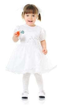 Leuk meisje in feestelijke witte jurk houdt zeepbellen in handen