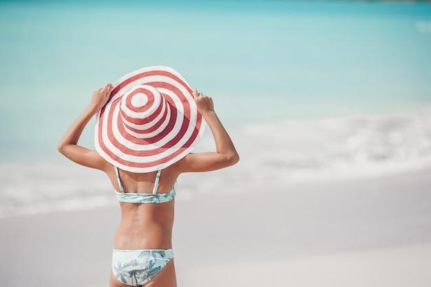 Leuk meisje in hoed bij strand tijdens caraïbische vakantie