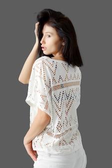 Leuk meisje in kanten blouse aanraken van haar haren.