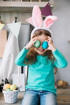 Leuk meisje in konijntjesoren die gekleurde eieren houden bij ogen