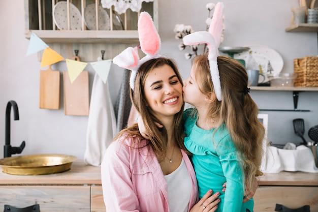 Leuk meisje in konijntjesoren die moeder op wang kussen