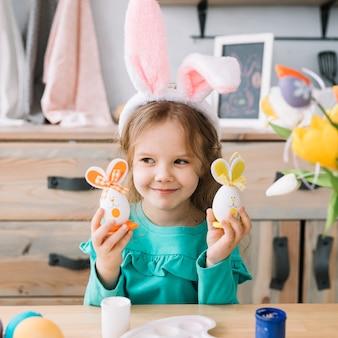 Leuk meisje in konijntjesoren die paaseieren houden