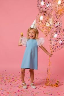 Leuk meisje in kostuum met ballonnen en feestmuts