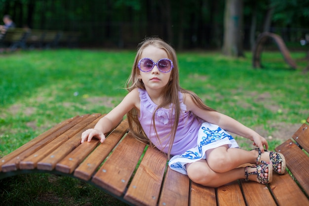 Leuk meisje in purpere glazen die op houten stoel liggen openlucht
