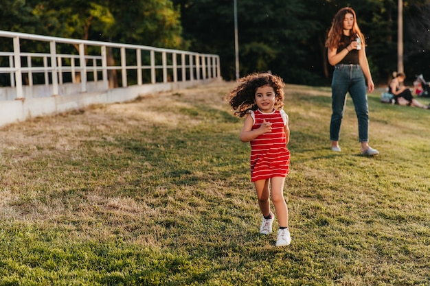 Leuk meisje in rode kleding die in park loopt. charmante jongen met krullend haar spelen op gazon.