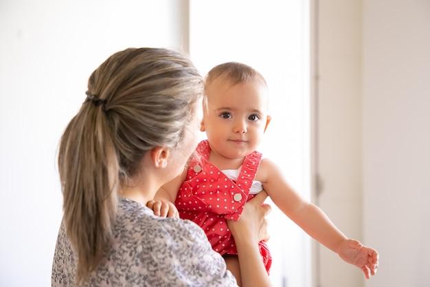 Leuk meisje in rood pak zittend op moeder handen. achteraanzicht van zorgzame moeder dochter te houden en met haar te praten. familie tijd, moederschap en thuis zijn concept