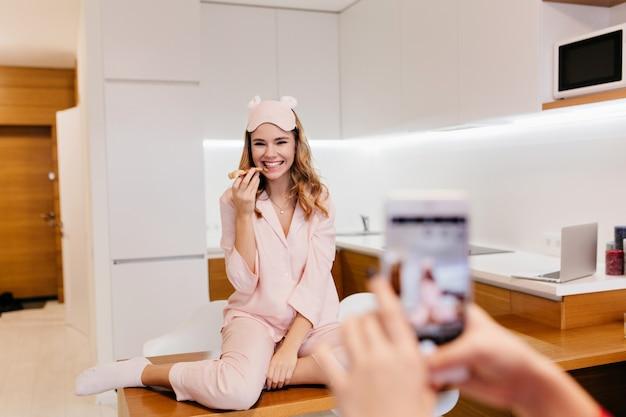Leuk meisje in roze nachtkostuum pizza eten met plezier tijdens fotoshoot. portret van glimlachende krullende dame met smartphone op voorgrond.