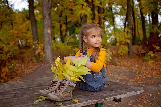 Leuk meisje in schoenen in hipsterstijl met heldere binnen bladeren
