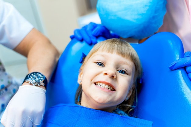 Leuk meisje in tandheelkundige kliniek. kind in stomatologisch kabinet met open mond.