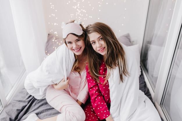 Leuk meisje in trendy roze slaapmasker zittend op bed in de buurt van vriendin. geïnteresseerde donkerharige jonge vrouw in rode nachtkleding poseren met deken.