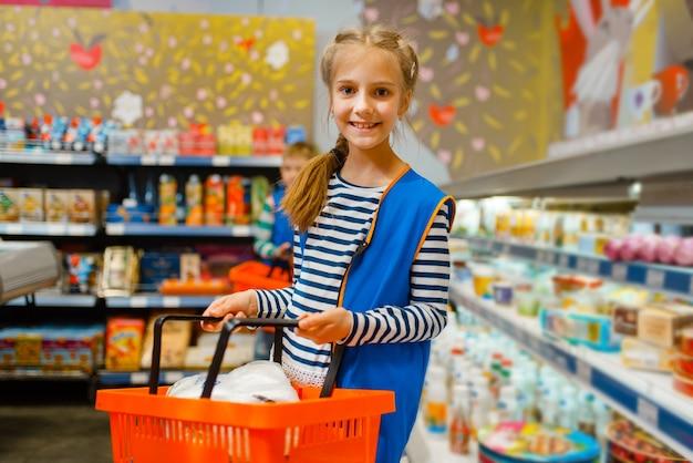 Leuk meisje in uniform met mand spelen verkoopster, speelkamer. ki