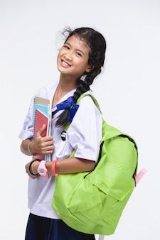 Leuk meisje in uniform van de student met kantoorbehoeften op grijs