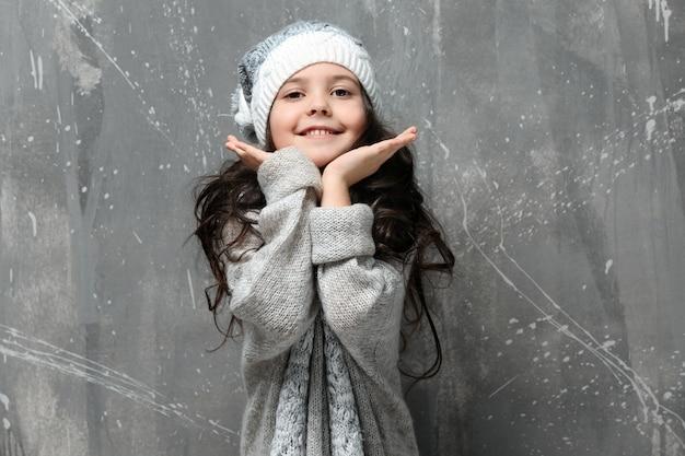 Leuk meisje in warme kleren op grungemuur