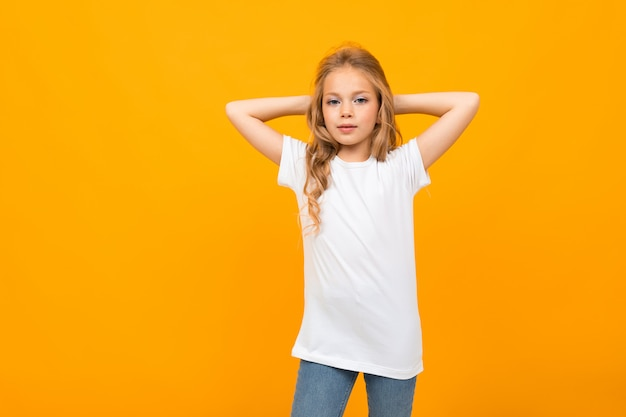 Leuk meisje in wit t-shirt gebarende en glimlacht op witte muur