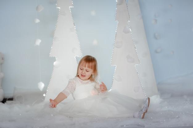Leuk meisje in witte prinses kostuum tussen witte kunstmatige gloeiende kerstbomen