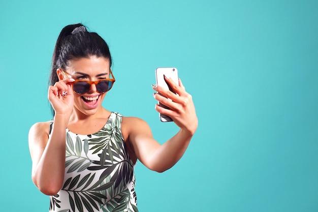 Leuk meisje in zonnebril poseren in de studio nemen een selfie op de telefoon