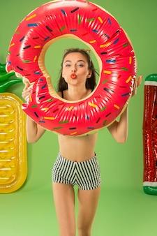 Leuk meisje in zwembroek poseren in de studio. zomer portret kaukasische tiener op een groene achtergrond.