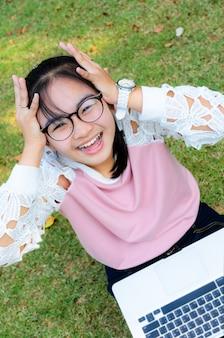 Leuk meisje is blij met notitieboekje op gras in park