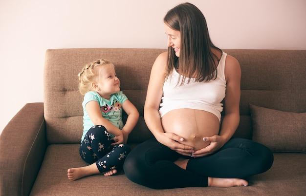 Leuk meisje kijkend naar lachende zwangere moeder en lachen