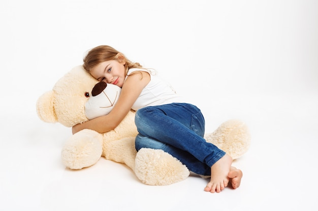 Leuk meisje liggend op de vloer met speelgoed beer knuffelen.