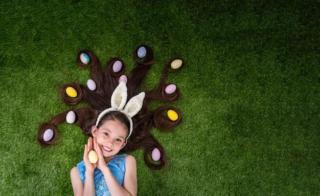 Leuk meisje liggend op het gras met paaseieren. paaseieren zitten in haar haar.