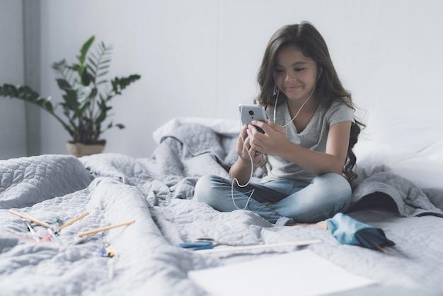 Leuk meisje luistert muziek in hoofdtelefoons in de slaapkamer