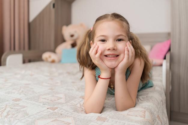 Leuk meisje maakt grappige gezichten op het bed