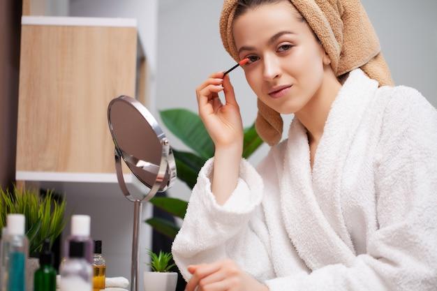 Leuk meisje maakt make-up op het gezicht in de badkamer