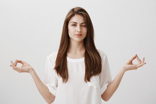 Leuk meisje mediteren maar nieuwsgierig met één oog gluren
