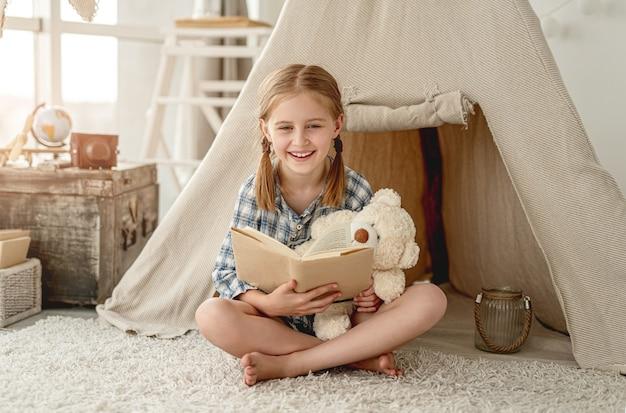 Leuk meisje met beer en papieren boek zittend op de vloer van de kamer versierd met wigwam, kist en retro lantaarn