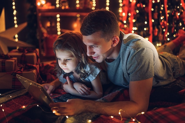 Leuk meisje met behulp van tablet met papa thuis.