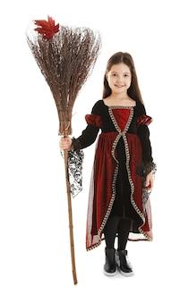 Leuk meisje met bezem in halloween-kostuum op licht