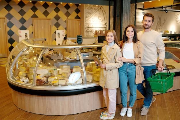 Leuk meisje met blocnote en haar ouders die u terwijl status door kaasvertoning in supermarkt kijken