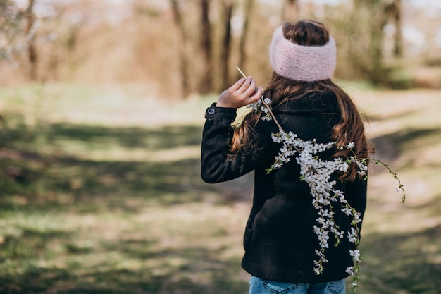 Leuk meisje met bloeiende brench in park