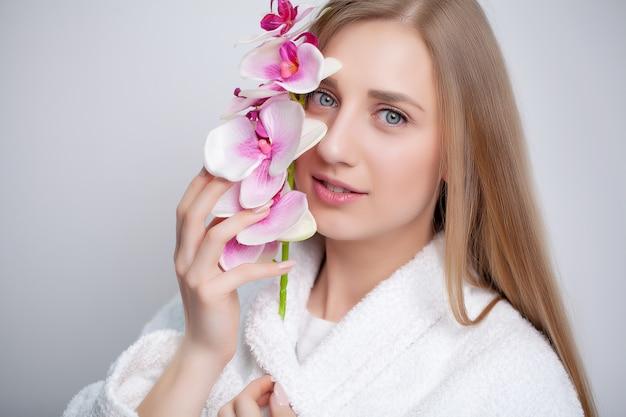 Leuk meisje met bloemen na het nemen van een douche