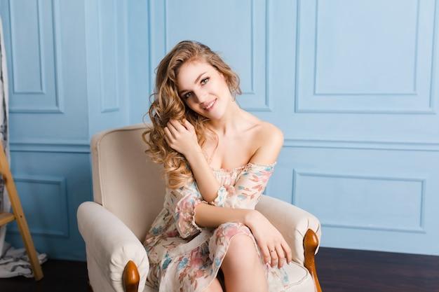 Leuk meisje met blond krullend haar zit op fauteuil
